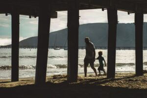 Father and son walking under boardwalk